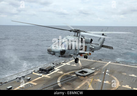 South China Sea, August 6, 2014 - An MH-60R Sea Hawk helicopter lifts off from the guided-missile destroyer USS - Stock Photo