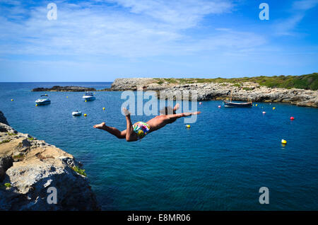 Cliff diving in the habour of the traditional small town of Binibequer Vell, on the Spanish island of Menorca, in - Stock Photo