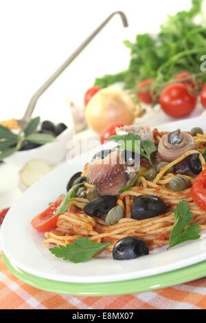 Spaghetti alla puttanesca with olives and anchovies - Stock Photo