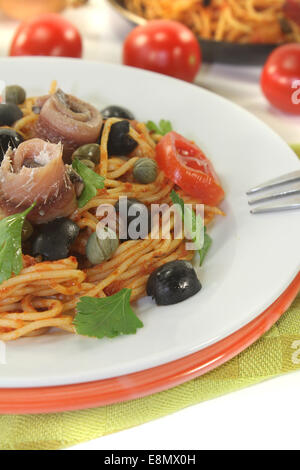 Spaghetti alla puttanesca with olives, capers and anchovies - Stock Photo