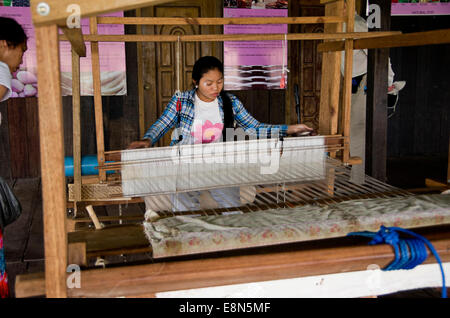 Young woman weaves lotus thread into cloth on a large loom - Stock Photo
