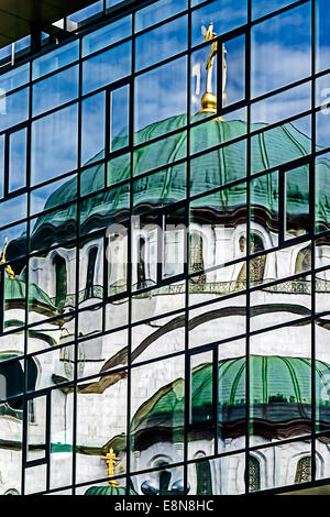 Old and new in the mirror. Cathedral St. Sava in Belgrade, reflected in the glass wall of a modern building. - Stock Photo