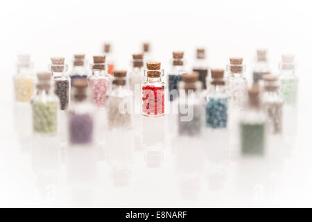 Tiny glass bottles with a cork stopper, filled with colorful of beads, on a white background using selective focus - Stock Photo