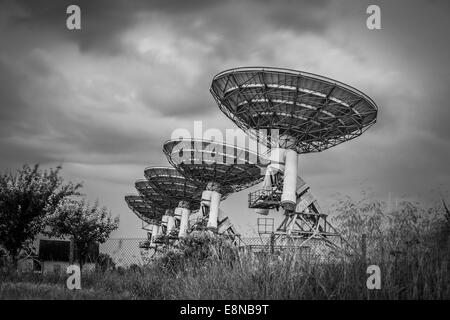 Radio telescope satellite dish array in a barley field before a storm in black and white - Stock Photo