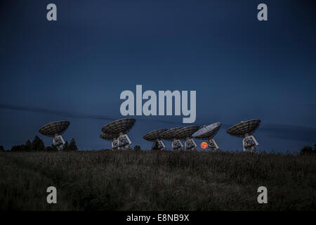 The full moon rises over the horizon behind a radio telescope array as the sun sets - Stock Photo