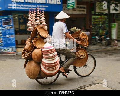 Vietnamese hat vendor on his bicycle in Hanoi, Vietnam - Stock Photo