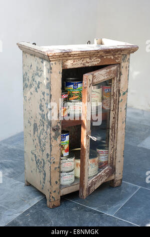 Picture by Roger Bamber : 30 June 2014 : An old battered Indian Tin food cabinet full of tinned food. - Stock Photo
