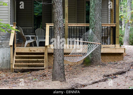 Hammock slung between two trees in front of a cottage in Grand Bend, Ontario Canada - Stock Photo