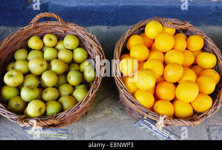 Fruit baskets containing oranges and russet apples - Stock Photo