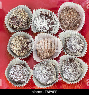 Homemade chocolate truffles with different coatings such as coconut, crushed almonds or hazelnuts or walnuts. - Stock Photo