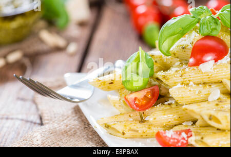 Portion of Pasta (Penne with Basil Pesto) on wooden background - Stock Photo