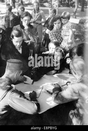 The picture from a Nazi news report shows Sudeten German refugees who fled from Czechoslovakia being processed by - Stock Photo