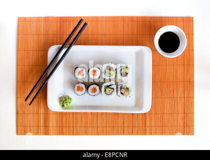Delicious sushi rolls on white plate with chopsticks - Stock Photo