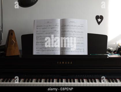 Metronome and manuscript on Piano - learning a musical instrument - Stock Photo