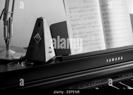 Metronome on Piano - learning a musical instrument - Stock Photo