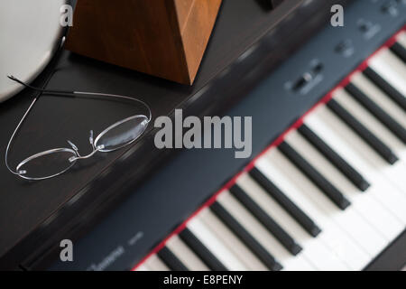 Glasses on Piano - learning a musical instrument - Stock Photo