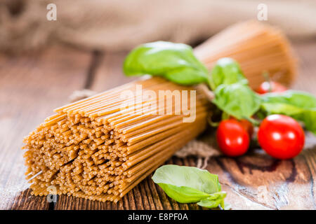 Wholemeal Spaghetti (close-up shot) on an old wooden table - Stock Photo