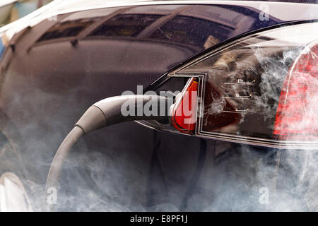 Electric car vs pollution - Stock Photo