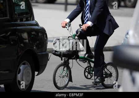 A city gent rides a folding cycle in London traffic - Stock Photo