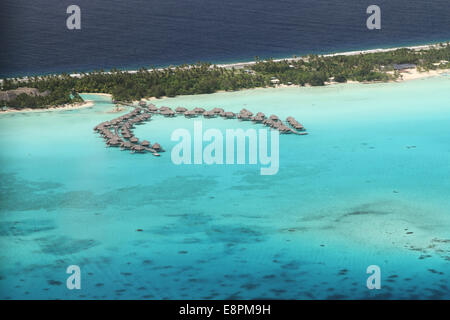 aerial view of motu and lagoon with over water bungalows - Stock Photo