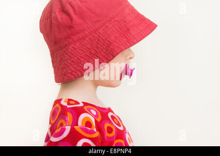 Profile portrait of little girl with red hat and pacifier - Stock Photo