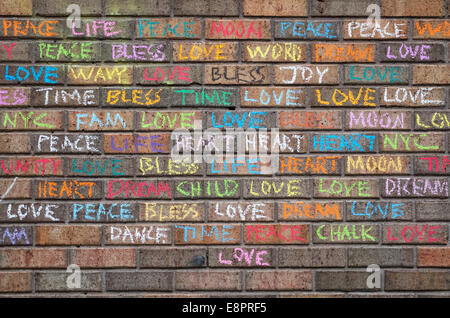 Positive one word messages written in colored chalk on a brick wall in New York City - Stock Photo