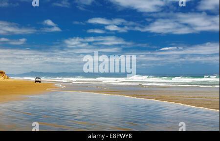 Car on the beach, Ninety Mile Beach, New Zealand - Stock Photo