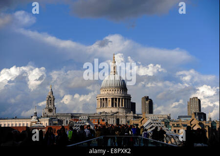 London UK - Visitors cross the Millennium footbridge with St Paul's Cathedral in the background - Stock Photo