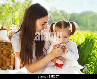 Happy young motherwith her baby at the spring picnic - Stock Photo