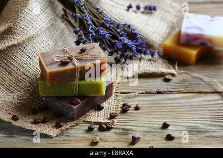 Handmade soap on wooden boards with coffee beans, toiletries close up - Stock Photo