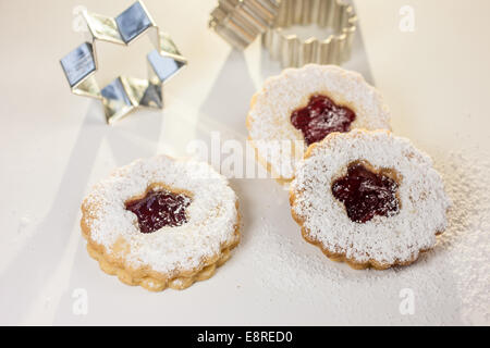 Christmas cookies and cookie cutters on white table - Stock Photo