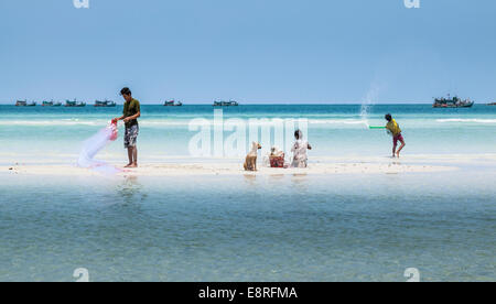 Fisherman with his two sons on a beach in Prek Svay, Koh Rong Island, Cambodia - Stock Photo