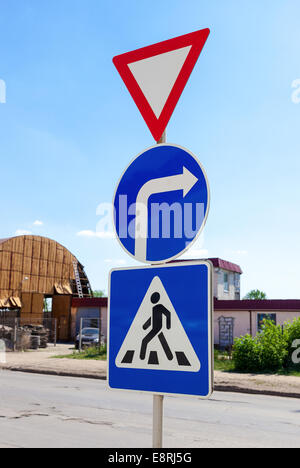 Triangular, round and square traffic signs above blue sky - Stock Photo