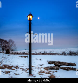 Light post and moon rising over a frozen lake - Stock Photo