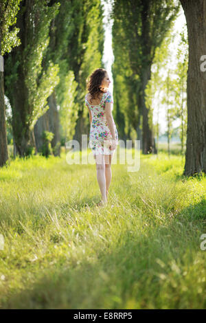 Shapely pregnant woman in the green park - Stock Photo