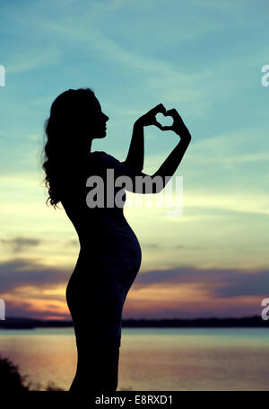 Pregnant mother making the heart sign - Stock Photo