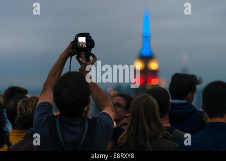 Tourists taking pictures of night Manhattan and Empire State Building from Rockefeller Center Observation Deck - Stock Photo