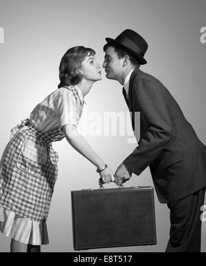 1950s 1960s HOMEMAKER WIFE IN CHECKED APRON KISSING BUSINESSMAN HUSBAND IN SUIT HAT AND TIE AS SHE HANDS HIM A BRIEFCASE - Stock Photo