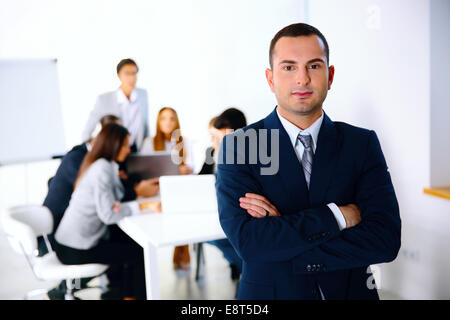 Portrait of a businessman standing in front of business meeting - Stock Photo