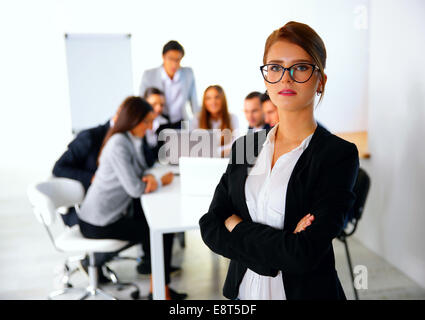Portrait of a businesswoman standing in front of a business meeting - Stock Photo