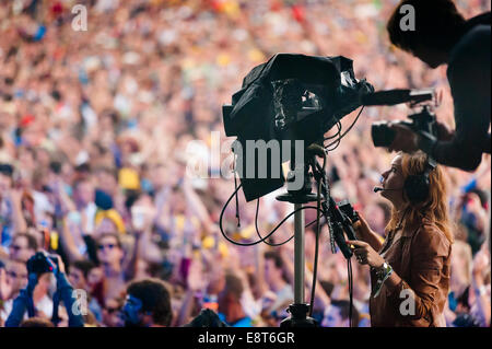 Professional girl cameraman with big camera on tripod filming at music festival - Stock Photo