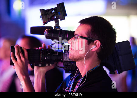 Professional cameraman with big camera on his shoulder filming concert - Stock Photo
