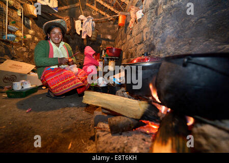Young woman cooking on an open fire in her traditional kitchen, Union Potrero, Quispillacta, Ayacucho, Peru - Stock Photo