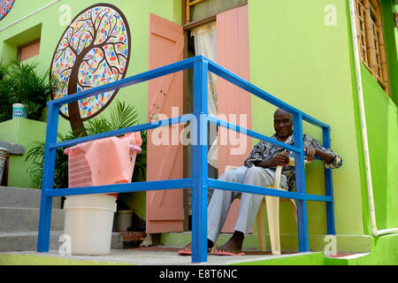 Old man sitting in front of a house he built with the support of a charity, Morne Hercule slum, Port-au-Prince, - Stock Photo