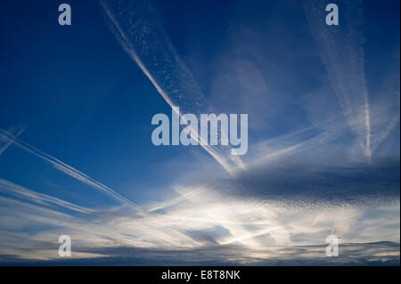 Small fluffy clouds, Cirrocumulus clouds, and medium-high stratus clouds, Altostratus, with contrails - Stock Photo