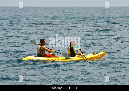 Young Couple Paddling A Cano In the Pacific. Catalina Island, California. - Stock Photo
