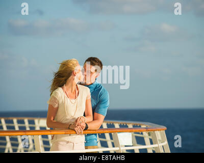 Caucasian couple kissing on boat deck - Stock Photo