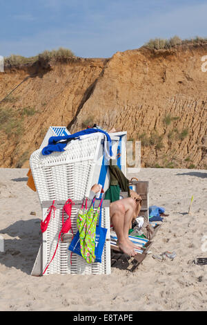 beach chair with legs sticking out, Red Cliff, Kampen, Sylt Island, Schleswig-Holstein, Germany - Stock Photo