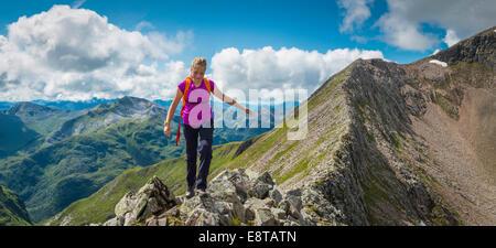 Caucasian girl hiking on rocky mountain - Stock Photo
