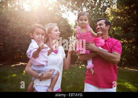 Parents holding children together in backyard